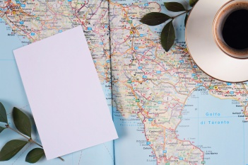 Map of Italy cup of espresso coffee and blank paper. Traveling and tourism background. Planning holiday or vacation concept